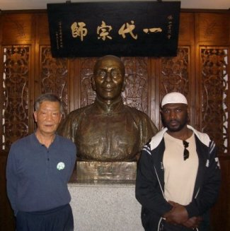 Grand Master Ip Ching and Sifu Garry McKenzie beside the bust of Grand Master Ip Man at the Ip Man Tong